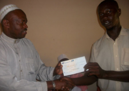 governor sanneh presenting cheque to dembo kambi